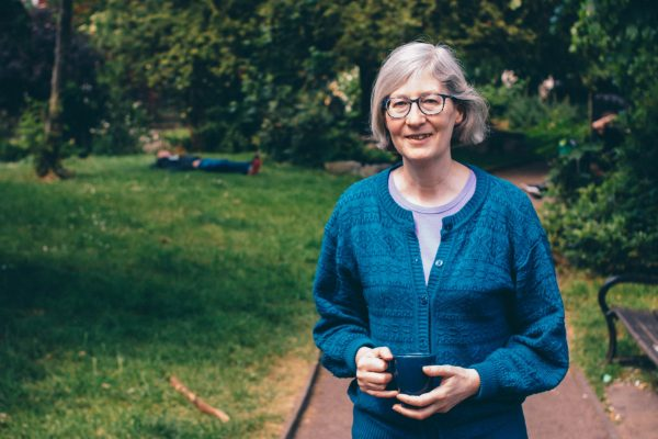 Photo of Anne from The Manna holding a coffee cup in a garden.