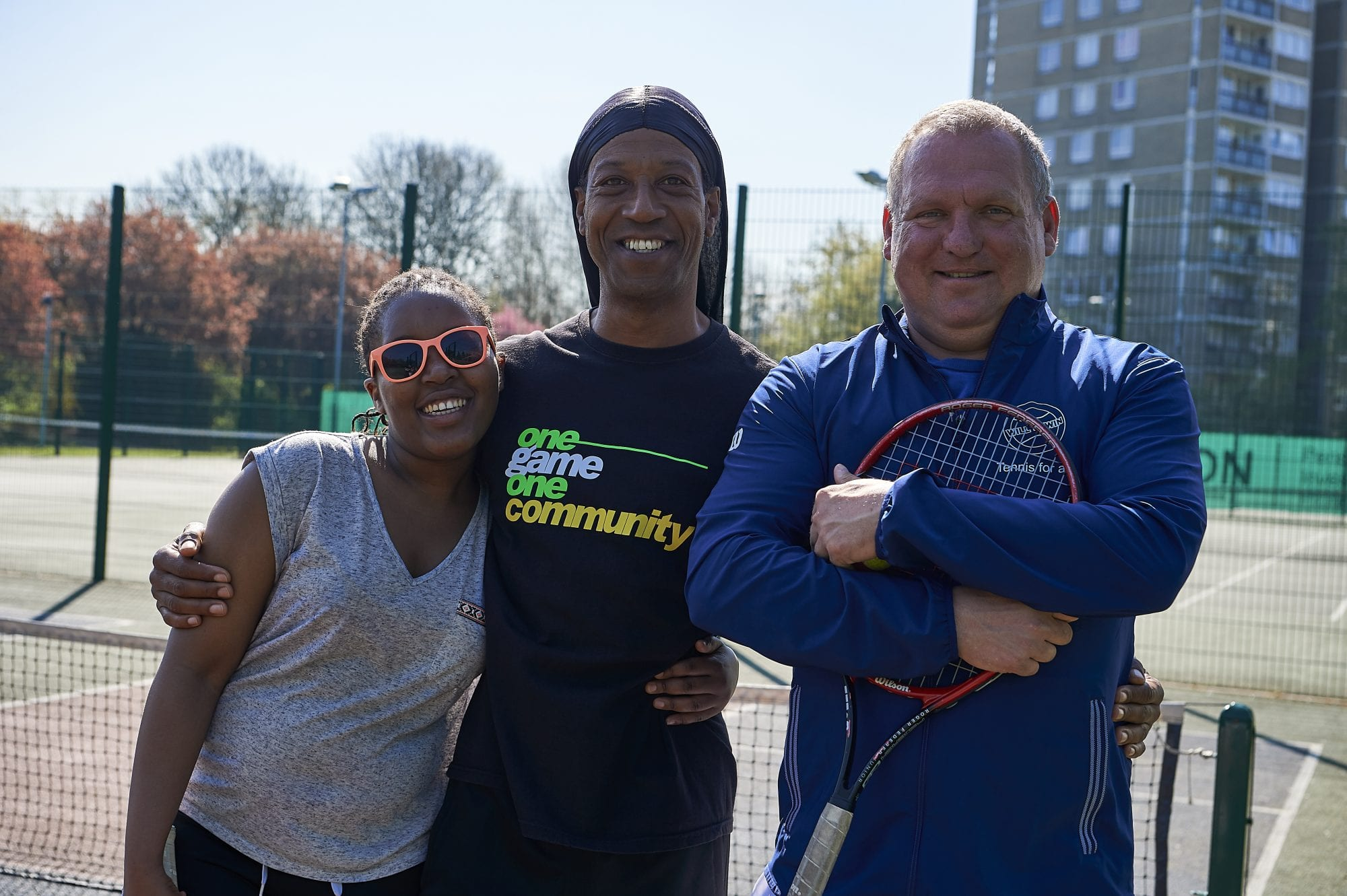 Image of 3 people standing on tennis court smiling
